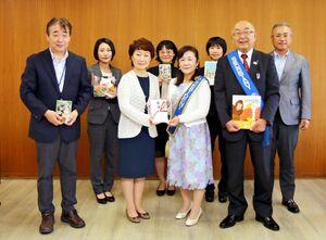 田原優子・多久市教育長(前列中央左)に目録を手渡した多久ロータリークラブの江里口尚子会長(同右)=市役所