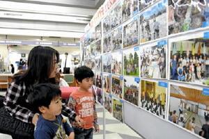 子ども交流を振り返るパネル展を見学する親子=鳥栖市役所