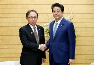 会談前に沖縄県の玉城デニー知事(左)と握手する安倍首相=19日午前、首相官邸