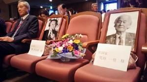 ステージ正面には作詞、作曲した栗原一登さんと團伊玖磨さんの遺影が飾られた。左は実行委員会の竹尾啓助会長