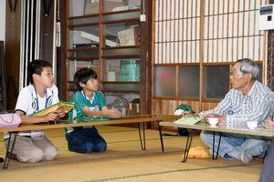 児童らは地域の高齢者たちに昔の地区の様子などを質問し、話を聞いた=佐賀市北川副町の江上公民館