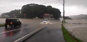 大雨で冠水して通行止めになった町道を通る車=6日午後2時25分ごろ、みやき町東尾