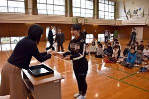竹下製菓の広告付き年賀はがきを6年生の藤田芽依さんに手渡す竹下真由社長=小城市の三里小