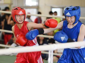 県高校総体に合わせて女子の試合も組まれた。ライトフライ級、唐津東の國元梨圭を攻める高志館の貞松優華(左)=佐賀市の県総合運動場ボクシング場