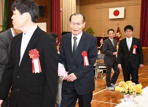 卒業式後、会場から拍手とお祝いの言葉を受ける山田健一さん(中央)=佐賀市の県立盲学校