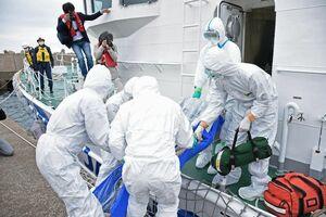 感染者役の男性を唐津海上保安部の巡視艇「やえぐも」に乗せる訓練参加者たち=唐津市鎮西町の加唐島