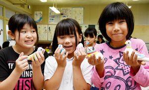 絵付けを終えた尾崎人形を手にする児童たち=神埼市の西郷小