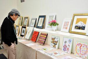 陶磁器や絵画など幅広い分野の作品に目をやる来場者=佐賀市の佐賀玉屋