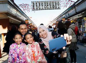 18日、東京・浅草の仲見世商店街で記念撮影するシンガポールから訪れた家族。2018年に日本を訪れた外国人旅行者は3千万人を突破した