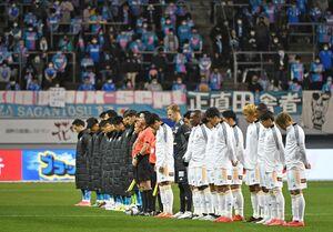 試合前に黙祷を捧げる鳥栖、仙台の両チームの選手たち=鳥栖市の駅前不動産スタジアム