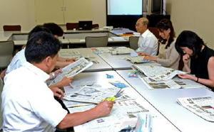 はさみを片手に回し読み新聞を体験する学校教諭ら=佐賀市の佐賀新聞社