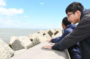 遠くに見える北方領土の島を眺め、思いをはせる生徒たち=北海道標津町