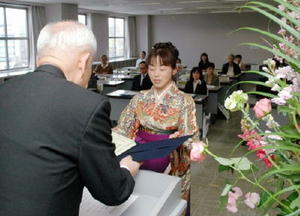放送大学佐賀学習センターの古賀和文所長(左)から証書を受け取る卒業生=佐賀市のアバンセ
