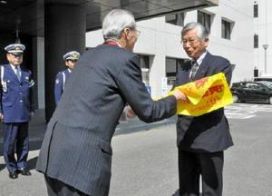 県交通安全協会の坂井会長(右)へ横断旗を手渡すときわ安全協力会の村木会長