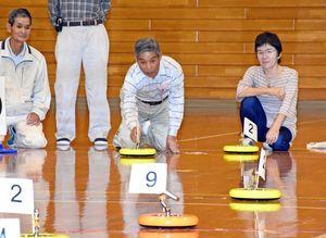 カローリングのジェットローラーを的に向かって投げる参加者=基山町総合体育館