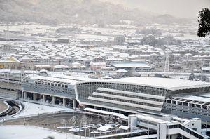 白く雪化粧した新鳥栖駅(手前)と鳥栖市の街並み=10日午前8時10分ごろ、鳥栖市の朝日山から撮影