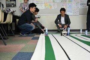 黒のラインに沿ってロボットを走らせるメンバーたち