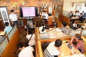 講師の326さん(中央奥)や参加者を前に行われたプレゼンテーション=佐賀市大財のジョイフル佐賀店