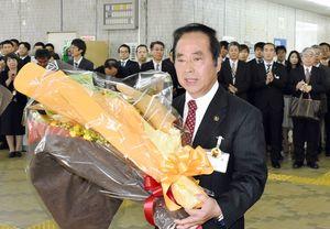 職員から受け取った花束を手に伊万里市役所を後にする塚部芳和氏
