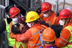 爆発事故で閉じ込められた地下の坑内から救出される作業員=24日、中国山東省(新華社=共同)
