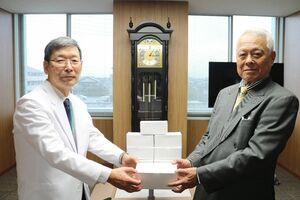 桐野髙明理事長(左)にマスクを手渡す篠原建設の篠原隆博会長=佐賀市の県医療センター好生館