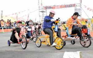 三輪車にまたがり、懸命にペダルをこぐ参加者=上峰町の三田川自動車学校跡地