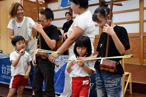 弓を引き、二胡を奏でる園児たち=佐賀市の保育園ひなた村自然塾