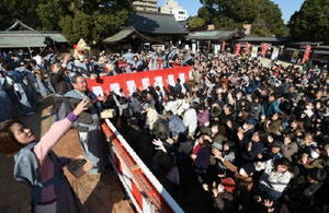 年男年女らがまく福豆をつかもうとする大勢の参拝客=佐賀市の佐嘉神社
