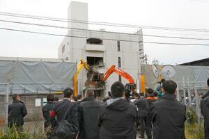 取り壊される工藤会の本部事務所を見つめる福岡県警の警察官ら=22日午前9時36分、北九州市