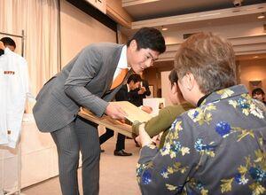 抽選会で参加者に賞品を手渡す古川侑利投手=武雄市の武雄センチュリーホテル