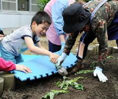 松原めばえ会の会員と笑顔でサツマイモの苗を植える子ども=佐賀市の金立特別支援学校分校舎