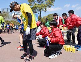 ランナーにスプレー式の鎮痛剤を吹きかける県柔道整復師会のメンバーたち=吉野ケ里歴史公園
