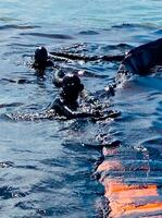 日本の大型貨物船から漏れた重油の拡散を防ぐダイバー=7日、モーリシャス沖(AP=共同)