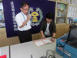 終業式で絵本の読み聞かせをする一番ヶ瀬徹校長(左)=佐賀市の金立小