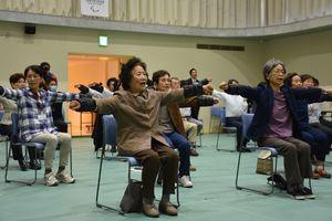 手首に重りを着けて体操する利用者=嬉野市塩田町の市社会文化会館「リバティ」