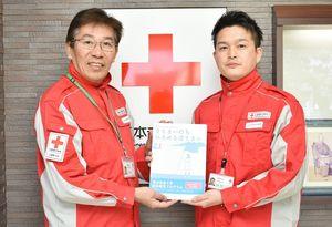防災教材の活用を呼び掛ける日本赤十字社県支部の馬渡幸秀主事(右)と秋山芳美さん=佐賀市の同支部