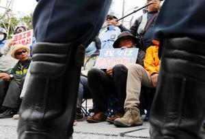 沖縄県名護市辺野古で、沿岸部への土砂投入に抗議し座り込む人たち=13日午後