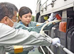 軽油の抜き取り調査を行う調査員=神埼市神埼町