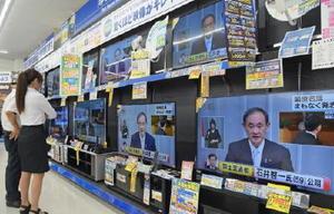 閣僚人事を発表する菅官房長官のテレビ放送に見入る人たち=3日午後1時30分ごろ、佐賀市のエディオン佐賀本店