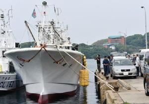 金塊とみられる積み荷を運んだ小型船を調べる唐津海上保安部の保安官や唐津署員ら=1日午後3時すぎ、唐津市鎮西町の名護屋漁港