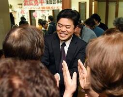 当選が確実となり、笑顔で支持者と握手を交わす武広勇平さん=12日午後10時26分、三養基郡上峰町坊所の事務所