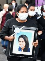 名古屋出入国在留管理局の施設収容中に死亡したウィシュマ・サンダマリさんの遺影を持つ妹のワヨミさん=16日午後、名古屋市守山区