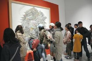 池田学さんの作品「興亡史」にじっくりと見入る来場者たち=佐賀市の県立美術館