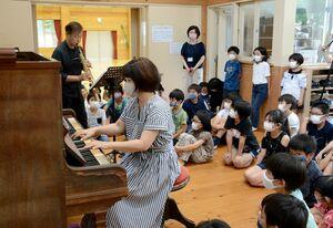 吉島環さんが演奏するピアノの音色に聞き入る児童たち=有田町の有田小