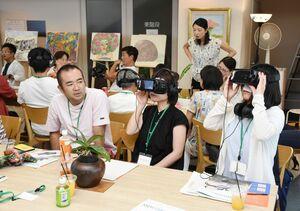 VR機器を使って自閉症の人の知覚を体験する参加者たち=基山町のピクファ