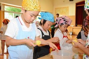 「チェー」作りに挑戦し、トウモロコシの実をちぎる園児たち=東松浦郡玄海町のあおば園