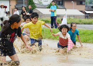 ドロリンピックで旗を取って笑顔を見せる児童たち=有田町の曲川小そばの水田