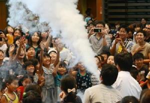液体窒素を使って積乱雲をつくる実験に歓声を上げる親子連れ=佐賀市のメートプラザ佐賀