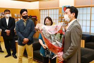 山口祥義知事(右)にバラを手渡した石川栄治さん(左から2人目)と奈津子さん(中央)=佐賀県庁