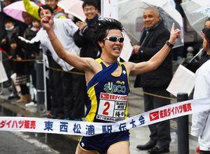 両手を掲げてゴールするSUMCO伊万里のアンカー梅田諒承選手=唐津市民会館前